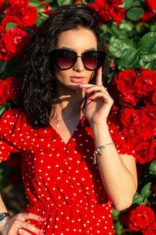 Красивая молодая женщина с модными украшениями и солнцезащитными очками в красном летнем платье стоит возле куста с розовыми цветами в солнечном свете
