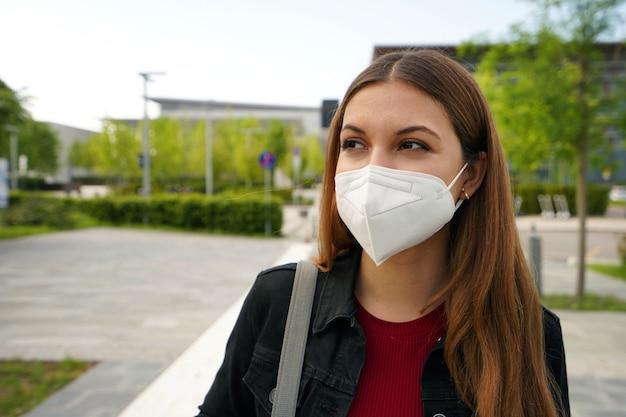 Ffp2 kn95 의료 마스크를 쓴 아름다운 젊은 여성이 거리에서 걱정스러운 표정을 짓고 있습니다.