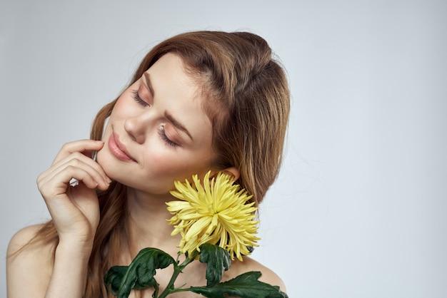 Красивая молодая женщина с цветком позирует в студии на светлом пространстве, романтическое нежное изображение, женский портрет