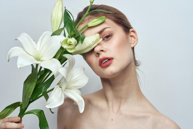 Красивая молодая женщина с цветком позирует в студии на светлой стене, романтическое нежное изображение, женский портрет