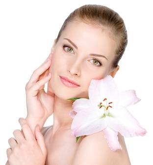 Bella giovane donna con il fiore su una spalla accarezzando il suo viso chiaro - isolato su bianco