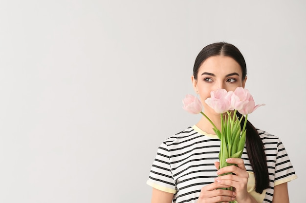 Beautiful young woman with flowers on grey surface