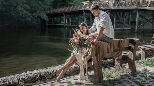 A beautiful young woman with flowers and her husband are sitting on a bench and enjoying communication, a date in nature, romance in marriage.