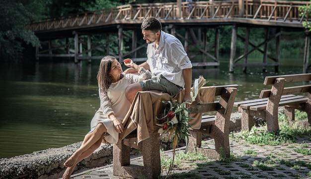 Una bellissima giovane donna con fiori e suo marito sono seduti su una panchina e si godono la comunicazione, un appuntamento nella natura, il romanticismo nel matrimonio.