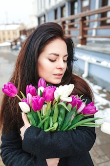 Beautiful young woman with flowers outdoor portrait, spring girl hold fresh bouquet, fashionable elegant lady , pretty brunette beauty female at city street