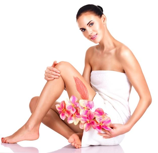 Bella giovane donna con fiori utilizzando uno scrub. isolato su bianco