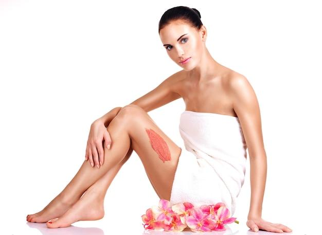 Bella giovane donna con fiori utilizzando uno scrub.