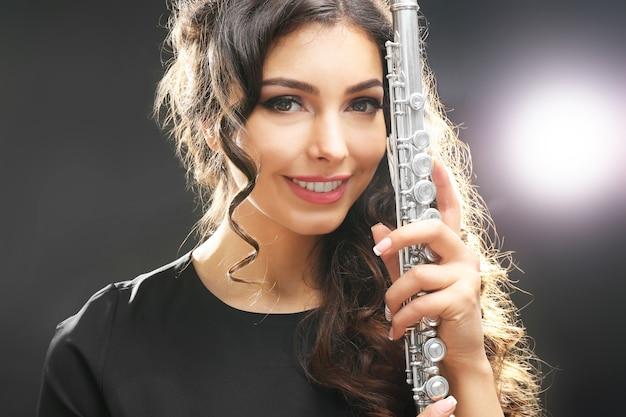 Красивая молодая женщина с флейтой на темной поверхности