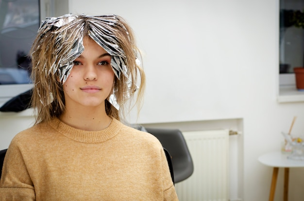 Beautiful young woman with foil on her hair