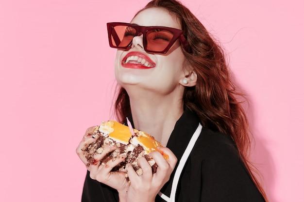 Красивая молодая женщина с едой в руках, женщина ест в студии, цветная поверхность, никаких диет
