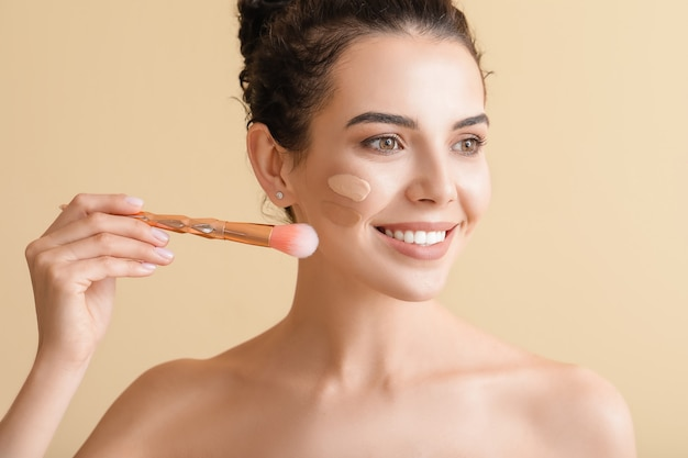 Beautiful young woman with foundation on her face on beige