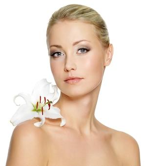 Bella giovane donna con pelle pulita fresca e fiore bianco sulla spalla - isolato
