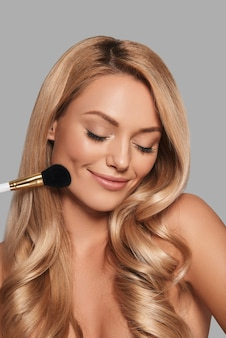新鮮な輝く肌と美容製品を適用し、灰色の背景に立って笑っている美しい若い女性