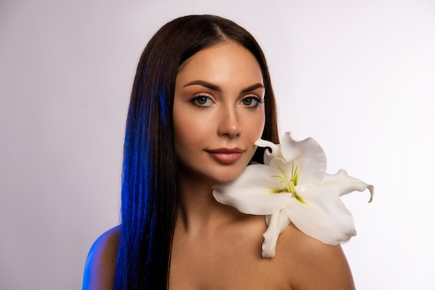 色の壁に新鮮なユリを持つ美しい若い女性。