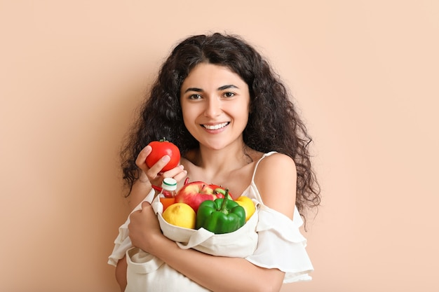 Beautiful young woman with fresh products in eco bag