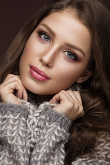 Beautiful young woman with gentle make-up in warm sweater and long straight hair