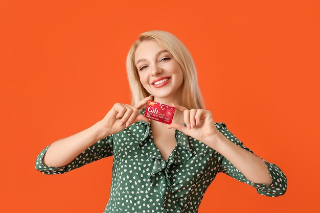 Beautiful young woman with gift card on color surface