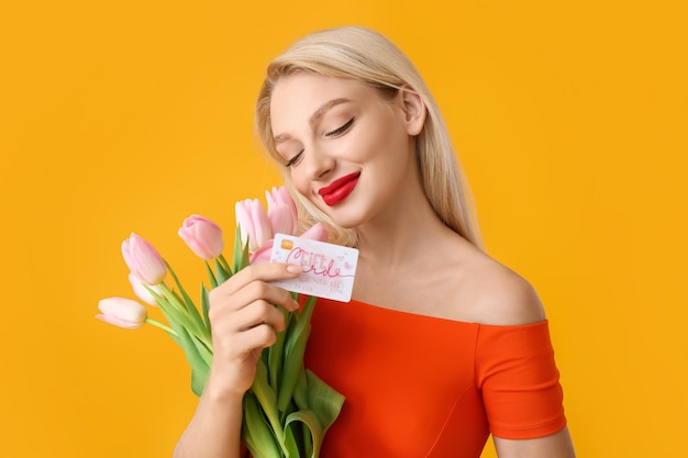 Beautiful young woman with gift card and flowers on color surface