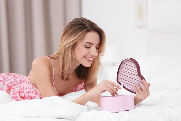 寝室で贈り物を持つ美しい若い女性。ロマンチックな驚き