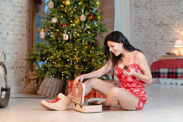 クリスマスツリーにプレゼントと美しい若い女性