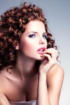 グラマーメイクと灰色の背景の上のスタジオでポーズをとるスタイリッシュな髪型を持つ美しい若い女性。