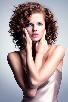 彼女の顔に触れる魅力的なメイクとスタイリッシュな髪型を持つ美しい若い女性。灰色の背景の上にスタジオでポーズをとるモデル。