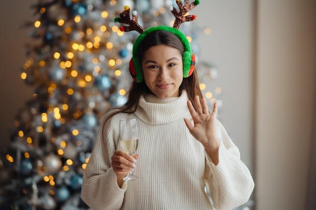 집에서 샴페인 한 잔과 아름 다운 젊은 여자. 크리스마스 축하