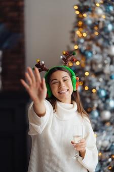 自宅でシャンパングラスを持つ美しい若い女性