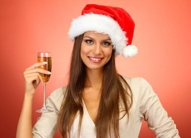 Красивая молодая женщина с бокалом шампанского, на красном фоне