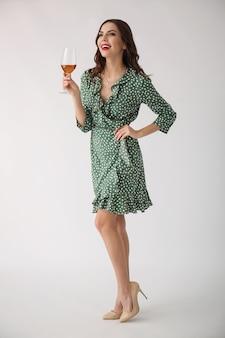 光の表面にワインのグラスを持つ美しい若い女性
