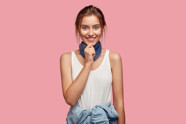 ピンクの壁にポーズをとってメガネと美しい若い女性