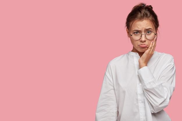 Красивая молодая женщина в очках позирует у розовой стены