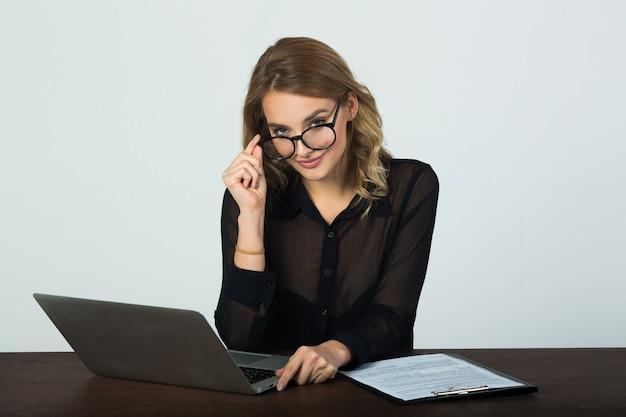 Красивая молодая женщина в очках сидит за столом с ноутбуком на белой стене