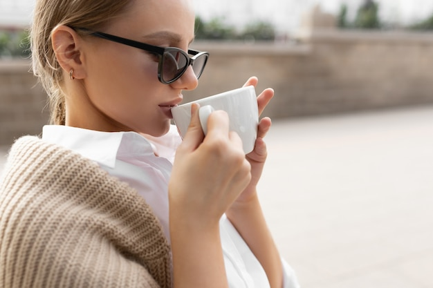 Beautiful young woman with glasses in a street cafe drinks coffee