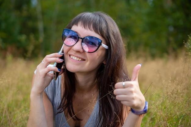 Красивая молодая женщина в очках разговаривает по телефону и улыбается молодая взрослая девушка, показывая большой палец