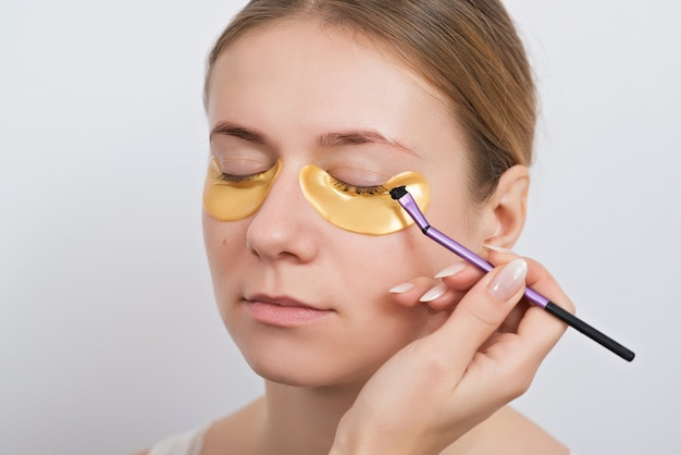 Beautiful young woman with gold hydrogel patches under eyes, isolated on white. skin care concept.