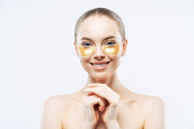 Beautiful young woman with golden patches under eyes, keeps hands pressed together