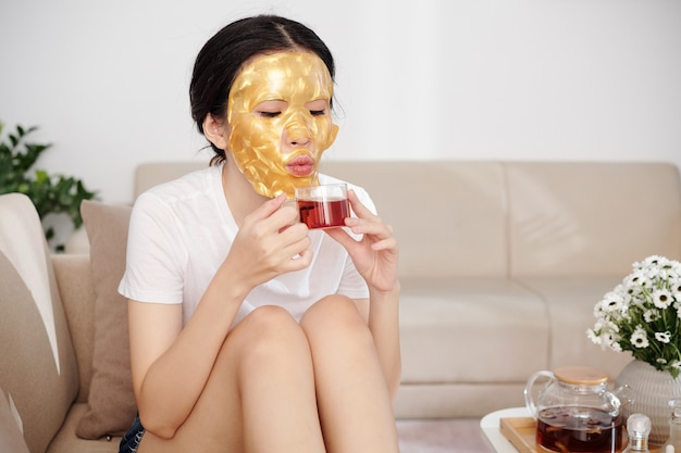 Beautiful young woman with golden silicone sheet mask on face sitting on sofa and blowing on cup of hot herbal tea