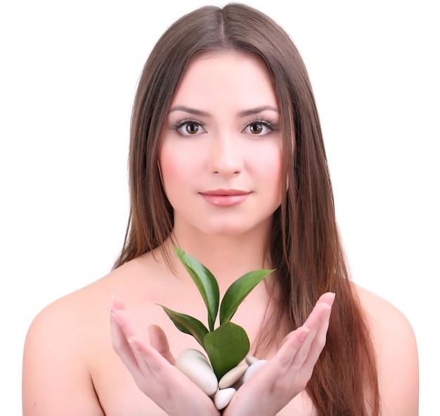 白で隔離緑の葉を持つ美しい若い女性