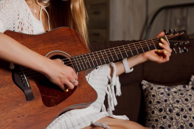 Красивая молодая женщина с гитарой в интерьере комнаты. милая женщина на диване с гитарой в руках. концепция домашнего обучения или игры на гитаре дома. место, защищенное авторским правом, для сайта, баннера или логотипа