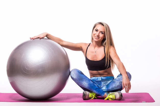 Beautiful young woman with gym ball exercising, isolated on white wall
