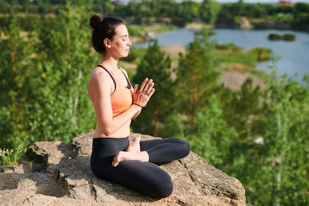 Beautiful young woman with hair bun concentrated on thoughts during meditation in mountains