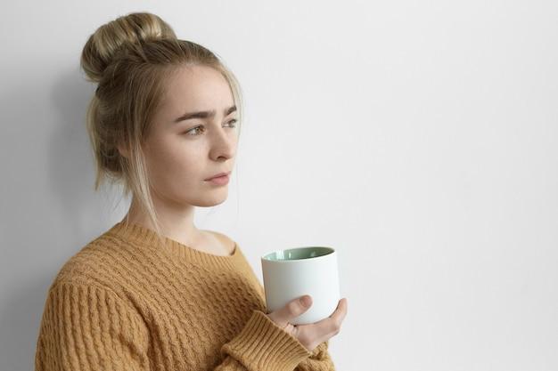 思いやりのある表情で彼女の前を見て、大きなお茶を持っている髪のお団子を持つ美しい若い女性。コーヒーを持っている居心地の良いセーターのかわいい女性