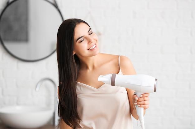 Красивая молодая женщина с феном в ванной комнате