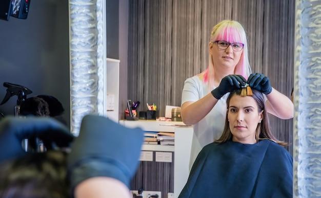 미용사가 머리 색깔을 바꾸기 전에 거울에서 머리 염색 샘플을 보고 있는 아름다운 젊은 여성