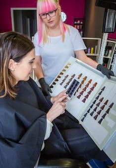 미용사가 스마트폰으로 머리 염색 팔레트에 사진을 찍는 아름다운 젊은 여성