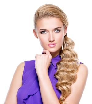 Красивая молодая женщина с рукой возле лица. фотомодель с длинными светлыми вьющимися волосами. изолированный на белой стене.