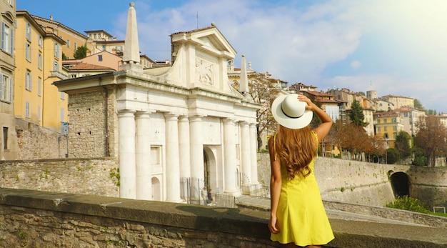 Красивая молодая женщина в шляпе, наслаждаясь видом со стен ворот порта сан джакомо и верхнего города бергамо, италия.