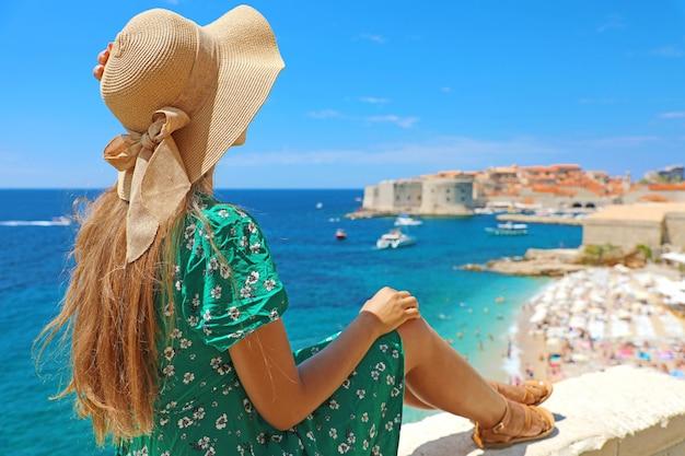 Красивая молодая женщина в шляпе, сидя на стене, глядя на потрясающий панорамный старый город дубровника в хорватии, европе