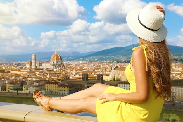 Красивая молодая женщина в шляпе, сидя на стене, глядя на потрясающий панорамный вид флоренции в тоскане, италия.